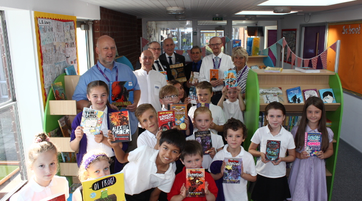 The Headmaster an d pupils proudly displaying some of their new books